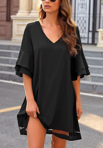 Angled shot of model wearing black flare sleeves mesh panel V-neckline shift dress