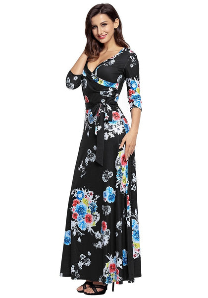Angled shot of model wearing black floral print boho long faux wrap dress
