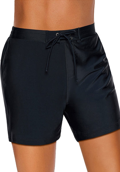 Angled shot of model wearing black lace-up board shorts