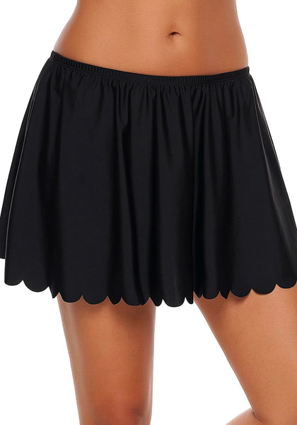 Angled shot of model wearing black scalloped hem swim skirt bottom
