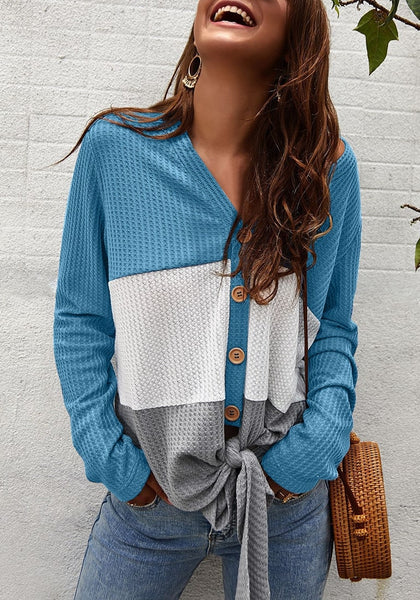 Angled shot of model wearing blue V-neckline button-up tie-front colorblock waffle knit top