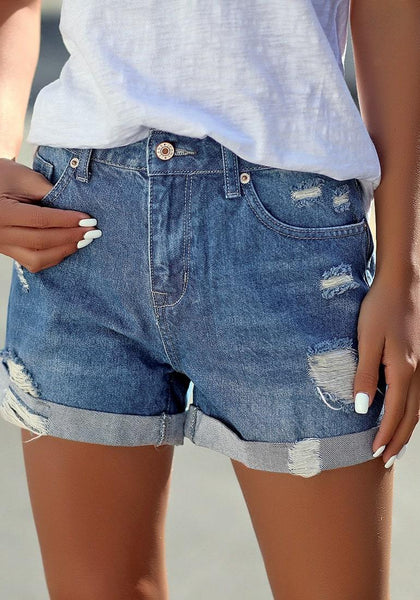 Angled shot of model wearing blue roll-over distressed denim shorts