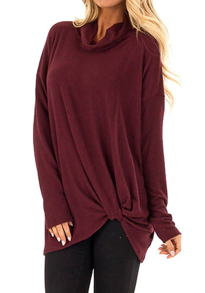 Angled shot of model wearing burgundy cowl neck side twist knot tunic top