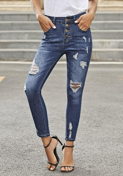 Angled shot of model wearing dark blue high-rise buttoned distressed denim skinny jeans