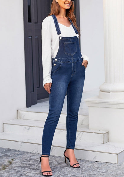 Angled shot of model wearing dark blue rolled hem skinny denim bib overall jumpsuit