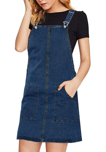 Angled shot of model wearing dark blue side pockets overall denim pinafore dress