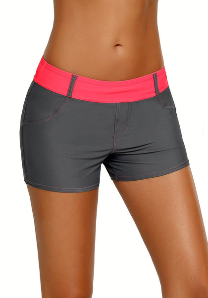 Angled shot of model wearing grey color block neon pink waistband swim shorts