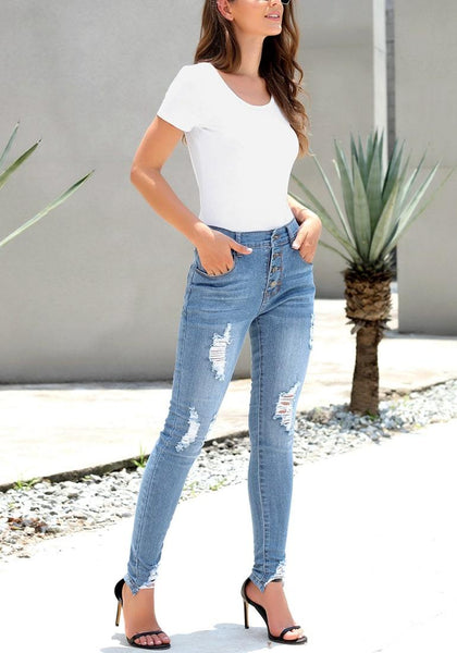 Angled shot of model wearing light blue high-rise ripped denim buttoned denim jeans