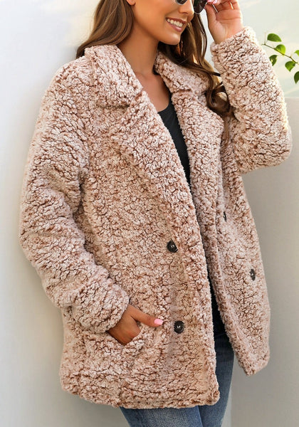Angled shot of model wearing light brown notched lapel double breasted fuzzy fleece coat