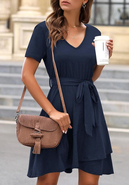 Angled shot of model wearing navy V-neckline short sleeves belted ruffle dress