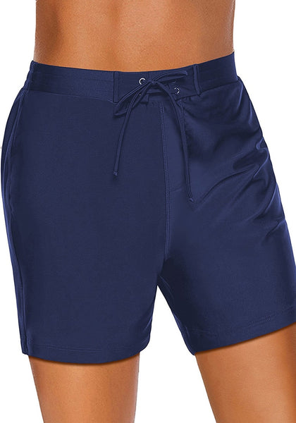 Angled shot of model wearing navy lace-up board shorts