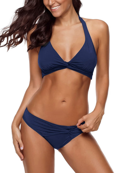 Angled shot of model wearing navy ruched self-tie halter bikini set