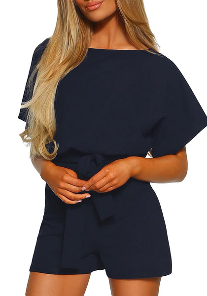 Angled shot of model wearing navy short sleeves keyhole-back belted romper