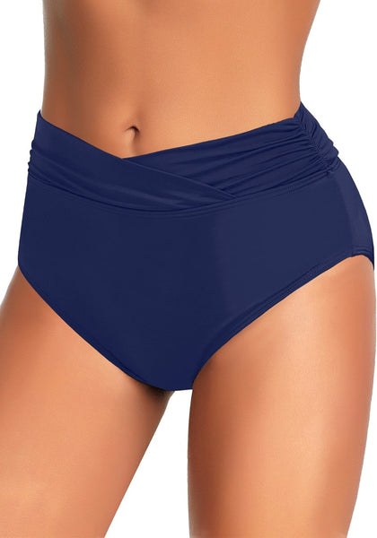Angled shot of model wearing navy surplice-waist ruched bikini bottom