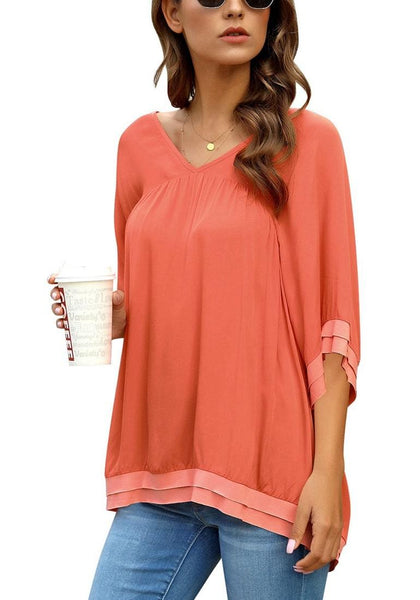 Angled shot of model wearing orange V-neck bell sleeves layered loose tunic top