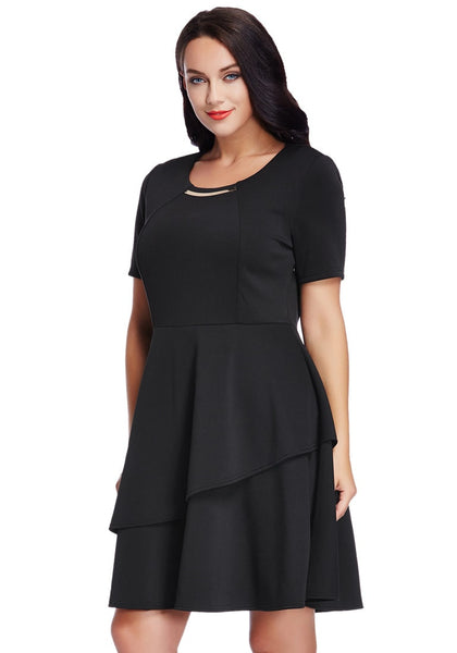 Angled shot of model wearing plus size black asymmetric layered skater dress