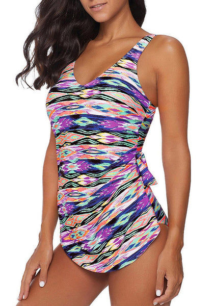 Angled shot of model wearing purple side-knot overlay abstract-print swimsuit