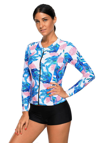 Angled shot of model wearing sky blue leaves print zipper-front swim top