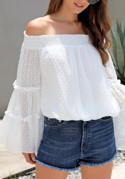 Angled shot of model wearing white bell sleeves dotted loose off-shoulder top