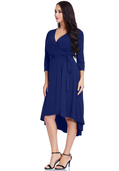 Angled shot of woman wearing plus size royal blue high-low wrap skater dress