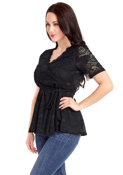 Angled side shot of model in plus size black scallop-neck lace blouse