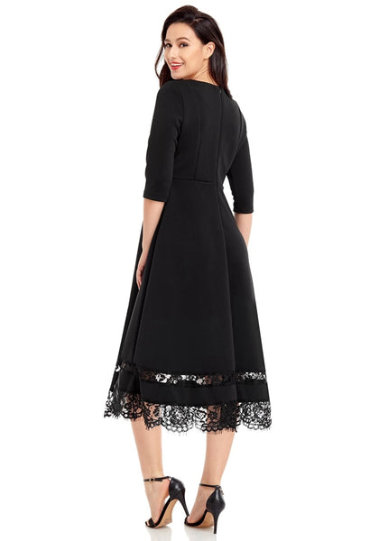 Angled side shot of model wearing black scallop hem lace panel skater dress