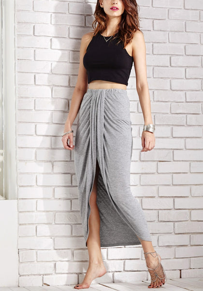 Angled side view of model in dark grey wrap maxi skirt
