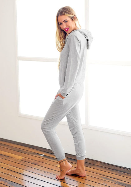 Angled side view of model in grey hooded pajama jumpsuit