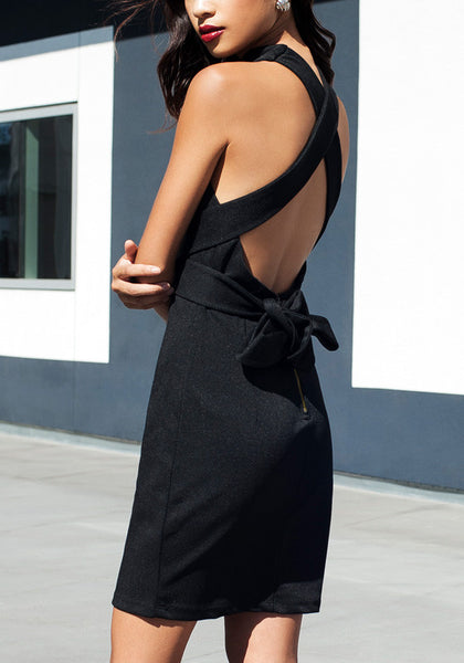 Angled side view of model in strappy black halter dress
