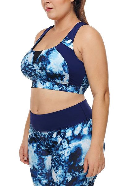 Angled side view of model wearing plus size blue abstract print crisscross-back sports bra