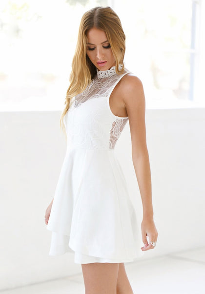 Angled view of lady in white lace illusion neck dress