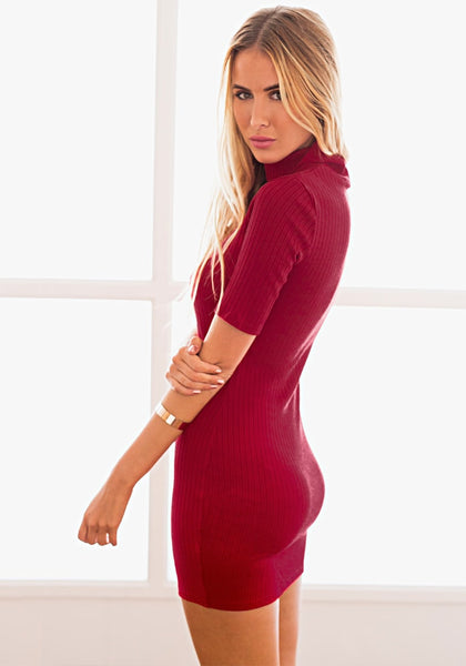 Angled view of model in a red ribbed turtleneck bodycon dress