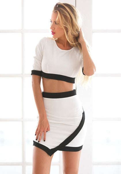 Angled view of model in black-lined white two-piece dress