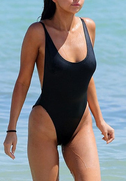 Angled view of model in black classic low-back swimsuit