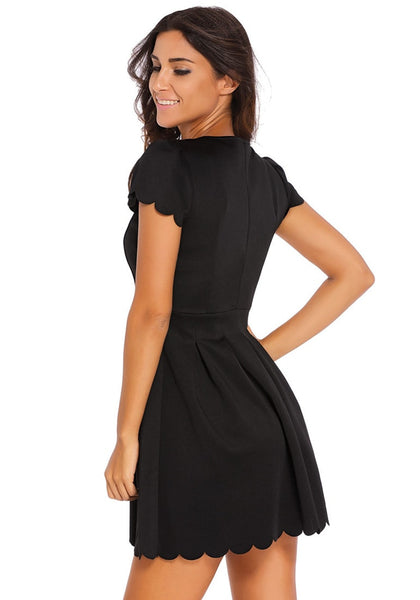 Angled view of model in black scallop hem skater dress