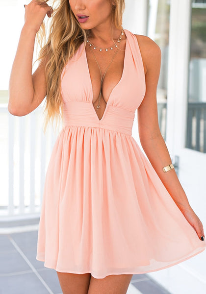 Angled view of model in pink plunge halter skater dress