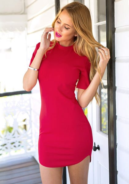 Angled view of model in red curved-hem bodycon dress