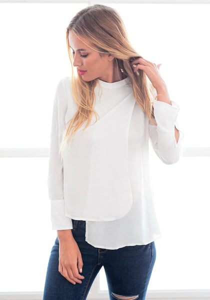 Angled view of model in white asymmetric layered chiffon blouse with one hand touching hair