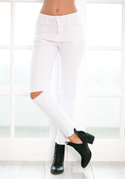 Angled view of model in white ripped skinny jeans