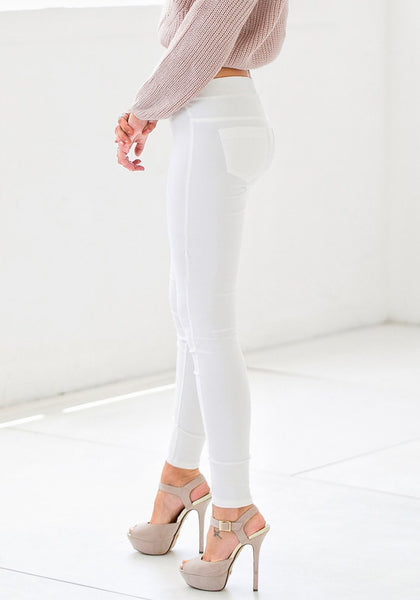 Angled view of model in white skinny high-waisted pants
