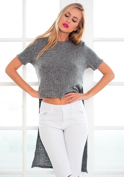 Angled view of  model wearing grey high-low knit top
