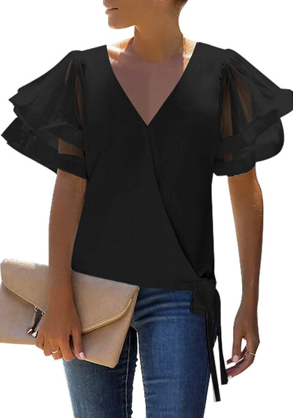 Angled shot of model wearing black V-back mesh butterfly sleeves side-tie wrap top