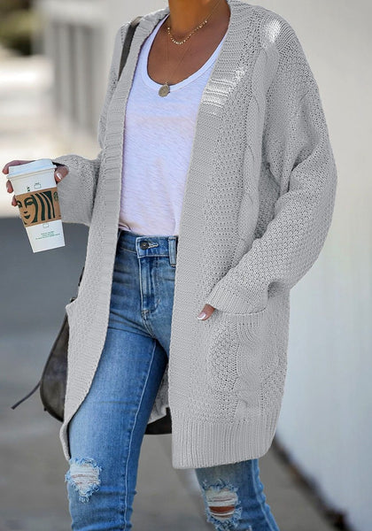 Model poses wearing grey open-front oversized cable knit cardigan