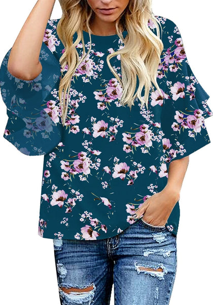 Angled shot of model wearing navy trumpet sleeves keyhole-back floral blouse