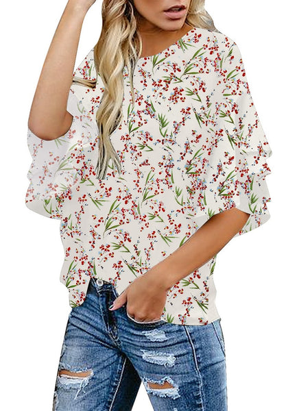 Angled side shot of model in off-white trumpet sleeves keyhole-back printed blouse