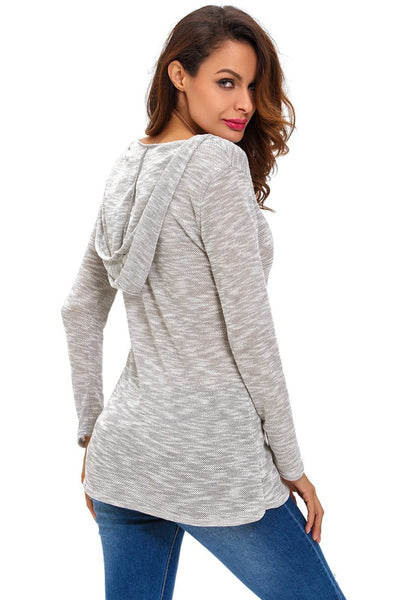 Back angle view of model in light grey hooded loose knitted top