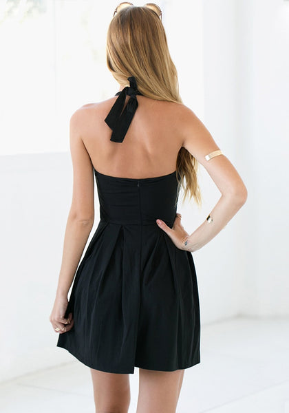 Back of model in black halter skater dress