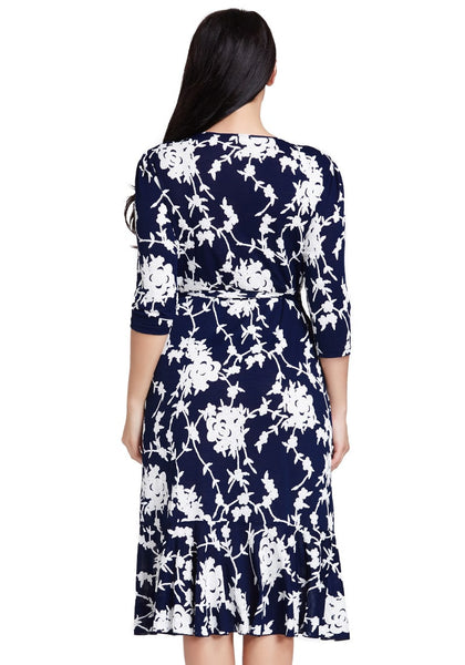 Back shot of model in plus size blue floral ruffled wrap dress
