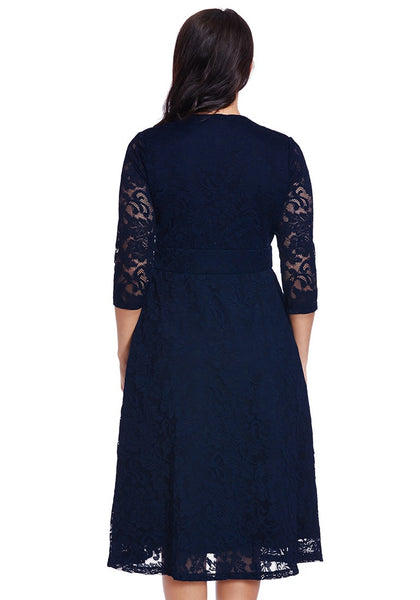Back shot of model in plus size navy lace surplice midi dress