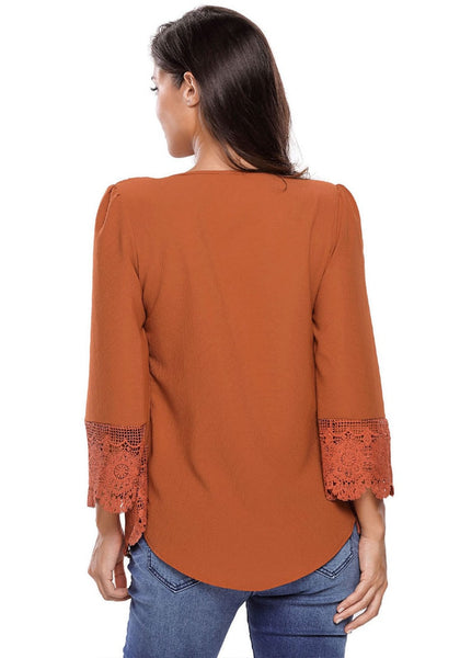 Back shot of woman in brown padded shoulder lace-trim blouse